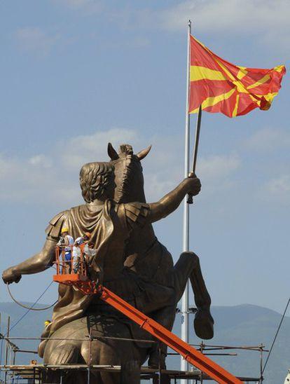 Varios trabajadores finalizan la colocación de la estatua de Alejandro Magno antes de que sea montada en un pedestal en la plaza central de Skopje