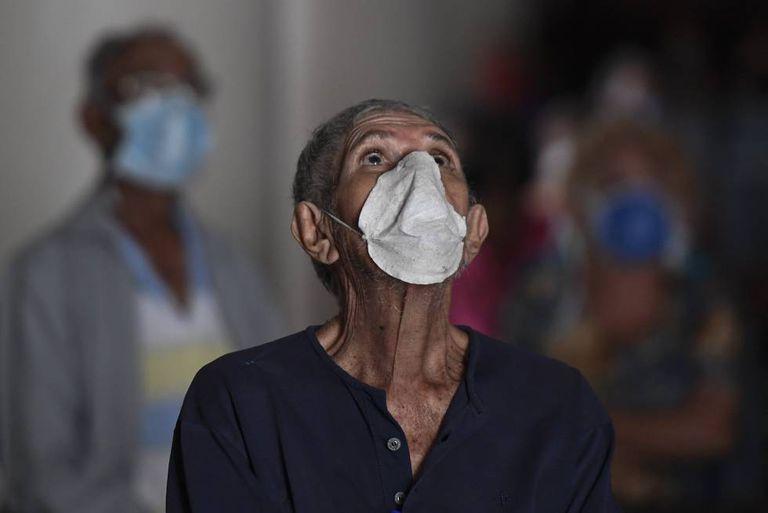 Un hombre con mascarilla reza en una iglesia de Caracas, en Venezuela.