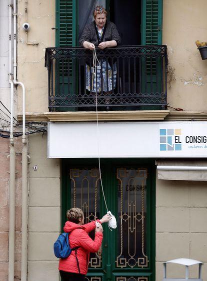 Una mujer facilita comida a una persona mayor gracias a una bolsa colgada de una cuerda desde su balcón.