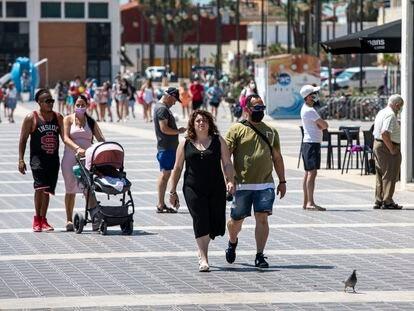Personas sin mascarilla y con ella en el paseo marítimo de la playa Malvarrosa de Valencia durante el primer día en el que no era obligado su uso.