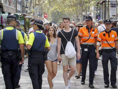 Agentes cívicos trabajan en la Rambla de Barcelona a un año de los atentados terroristas.