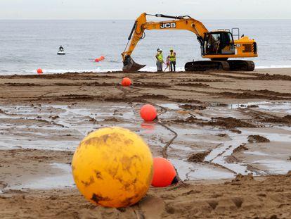 Unos operarios participan en las obras de tendido de un cable submarino de Google en Sopela (Bizkaia).