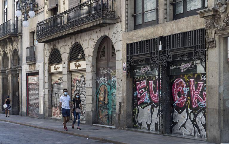 Una pareja pasea por la calle Ferran de Barcelona, con la mayoría de establecimientos cerrados.