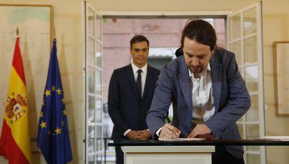 Detrás, el presidente del Gobierno, Pedro Sánchez,observa como el secretario general de Podemos, Pablo Iglesias, la firma el acuerdo presupuestario para 2019