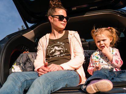 Una madre y su hija descansan en el maletero del coche.