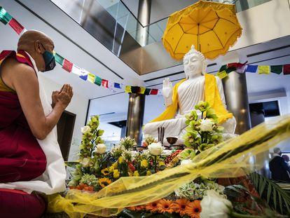 Un monje budista se arrodilla frente al buda en la ceremonia civil de su recepción en el Puerto de Valencia este martes