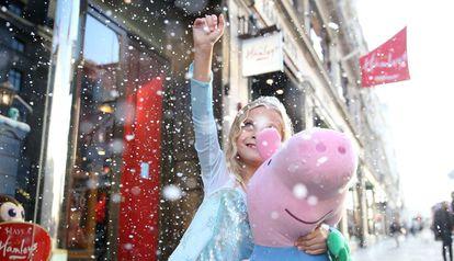 Una niña disfrazada de princesa sostiene un peluche de Peppa Pig.