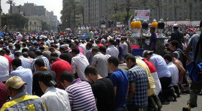 Miles de personas rezan durante una manifestación en la plaza; al fondo, la Mugamma.