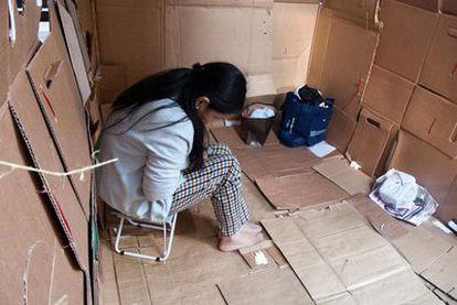 Una empleada doméstica se atrinchera tras unos cartones para pasar su día libre en Hong Kong.