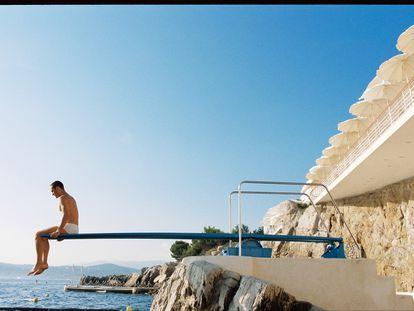 Muros encalados, roca,  el azul del cielo, del mar, y un turista sobre un trampolín de piscina. Pocas combinaciones cromáticas funcionan mejor.