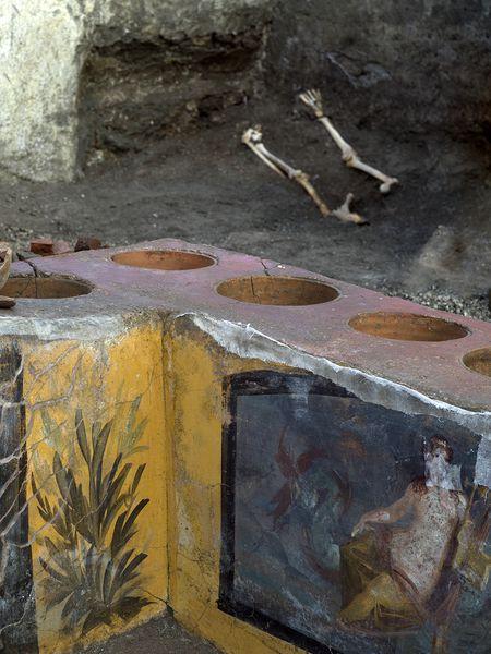 Detalle de la barra del 'termopolio' de Pompeya con restos humanos al fondo.