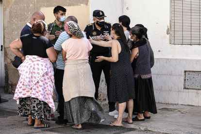 Un policía conversa con los vecinos afectados por el desalojo en Valencia, un miembro del Sindicato Construimos Malilla y un trabajador social.