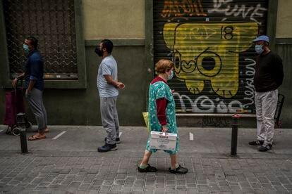 Reparto de alimentos organizado por la Asociacion Valiente Bangla en la calle Provisiones, 7 Madrid. Decenas de personas han hecho cola entre las 12 y las 14 horas a las puertas de la mezquita que ocupa ese local.Concepcion, de 86 años, vecina de la calle Provisiones, ha recibido algunos alimentos durante el reparto.  07/05/2020Madrid, España.