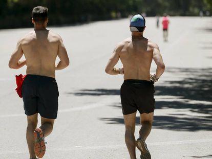 Dos hombres corren en el parque del Retiro de Madrid.