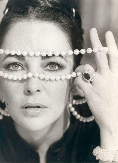 Elizabeth Taylor posa con un collar de perlas y un anillo, evocando su gran amor por las joyas