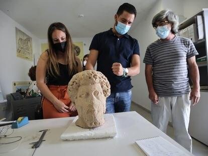 Los concejales Davinia Calderón y Daniel Caballero y el director del museo de Medina Sidonia, Salvador Montañés, inspeccionan una cabeza romana donada por Francisco Guerra.