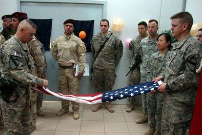 Soldados estadounidenses doblan la bandera durante una ceremonia de traspaso de las instalaciones militares al Ejército iraquí.