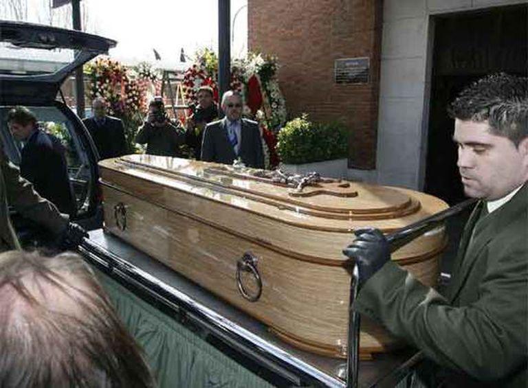 Empleados de los servicios funerarios portan el féretro que contiene el cuerpo del humorista, en el cementerio de La Almudena.