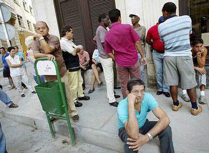 Varias personas esperan ante una oficina de cambio de divisas en La Habana.