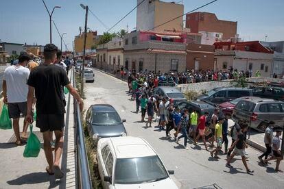 Unas mil personas que cruzaron la frontera el pasado mes de mayo recogen una bolsa de comida que les da diariamente la ONG Luna Blanca en la mezquita Sidi Embarek de Ceuta.