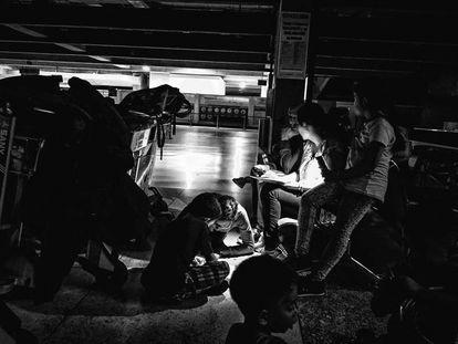 Un grupo de pasajeros en el aeropuerto de Maiquetía rellenan hojas de reclamación.