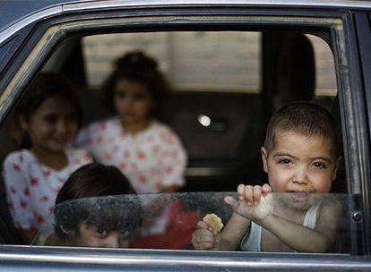 Niños miran por la ventana de un coche en Herat.