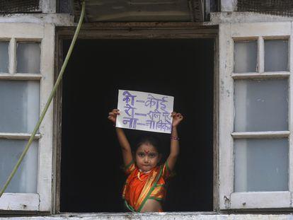 Una niña en Mumbai, India, muestra desde la ventana un cartel para pedir que nadie salga a la calle