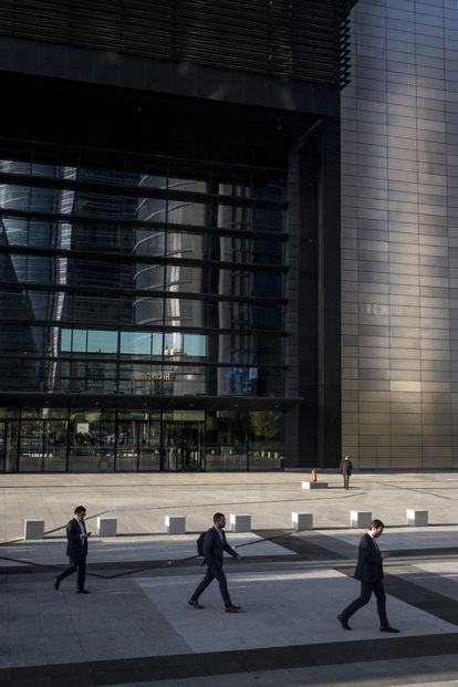 Varios hombres acuden a su puesto de trabajo en la zona de las Cuatro Torres de Madrid. Al fondo, la torre Cepsa.
