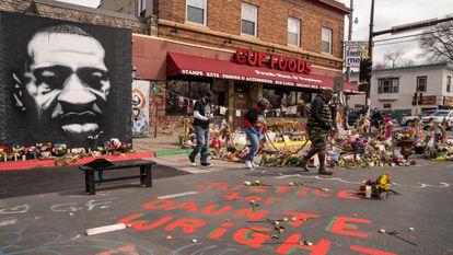 Unos visitantes observan las flores en recuerdo de George Floyd ante la fachada de Cup Foods, en Minneapolis, el 14 de abril.
