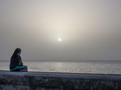 Una mujer contempla la tormenta de arena del Sáhara desde el Malecón de La Habana, Cuba.