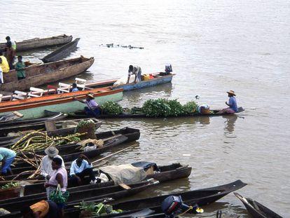 Agricultores en barcas transportando frutas por el río Atrato en Quibdó, Colombia.