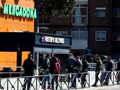 Colas a la entrada de un supermercado en Madrid durante la pandemia de coronavirus.