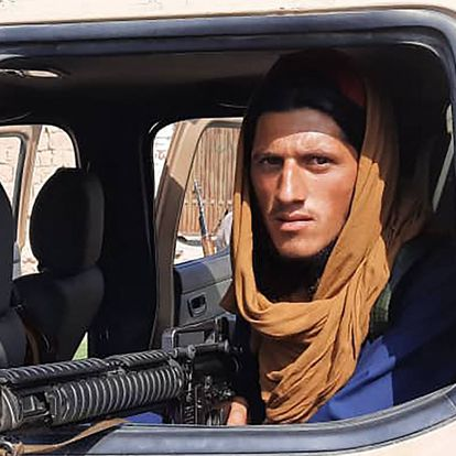 A Taliban fighter sits inside an Afghan National Army (ANA) vehicle along the roadside in Laghman province on August 15, 2021. (Photo by - / AFP)