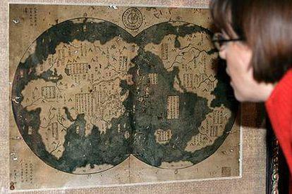 Una mujer examina atentamente el mapa que muestra las costas de medio mundo, y que supuestamente alcanzó en el siglo XV el navegante chino Zheng He. Entre ellas, la de América, a la que habría arribado siete décadas antes que Colón.