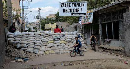 Unos niños pasan junto a una de las barricadas levantadas en la localidad de Cizre por jóvenes kurdos simpatizantes del PKK.