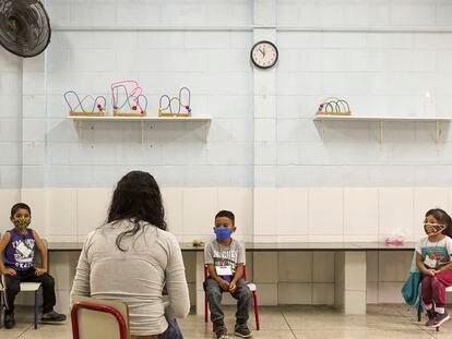 Una maestra da clase a tres de sus alumnos, todos separados por la distancia mínima de seguridad, en una escuela de educación primaria de São Paulo, en Brasil.