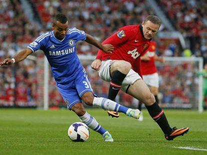 Cole y Rooney se disputan el balón.