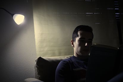 A young man reads a book under the light of a lamp in Madrid (Spain), on January 12.
