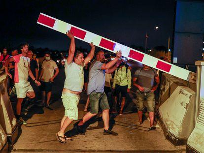 Un grupo de personas levanta las barreras de los peajes en la C-32, en la madrugada de este miércoles.