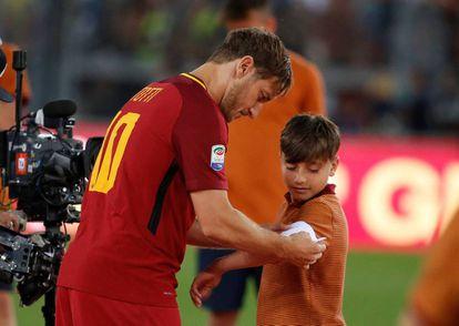 Totti cede su faja de capitán a un niño de los juveniles de la Roma tras su discurso de despedida.