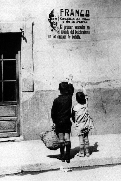 Dos niños saludan brazo en alto ante un cartel de Franco en septiembre de 1939.