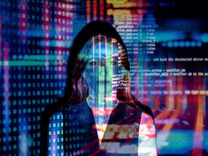 Una programadora frente a una pantalla con código informático.