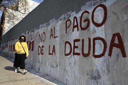 Una mujer pasa frente a una pintada contra el pago de la deuda, en Buenos Aires.