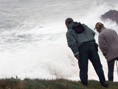 Dos personas se asoman al acantilado de Punta Langosteira (A Coruña), en el que una ola se tragó el lunes a tres personas.