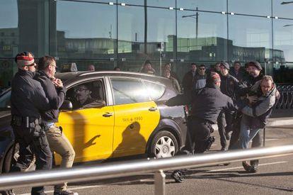 Agentes de los Mossos d'Esquadra retienen a dos taxistas en la segunda jornada de protesta contra el sistema de turnos en el aeropuerto de El Prat.