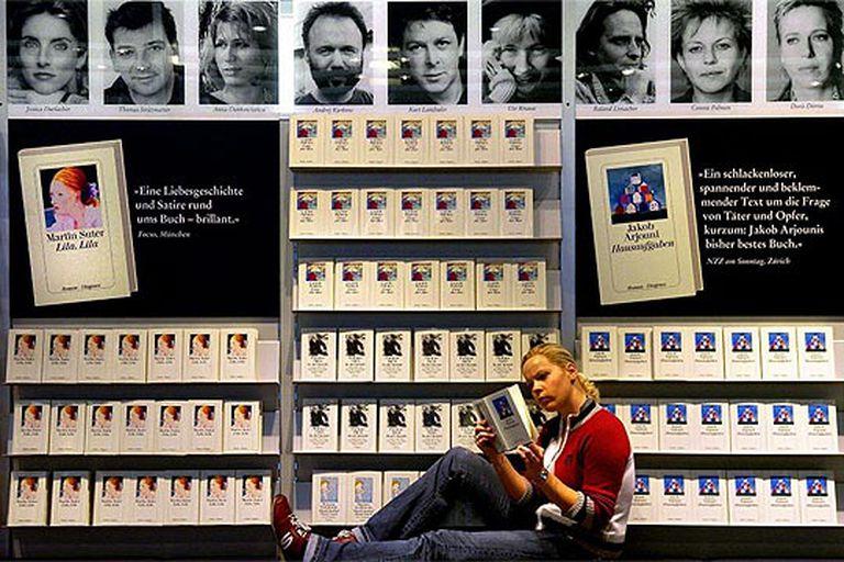 Una joven lee delante de uno de los expositores de la Feria del Libro de Fráncfort.