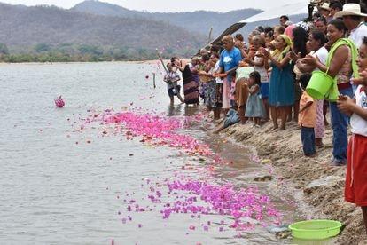 Habitantes de Paso de la Reina lanzan flores al Río Verde durante un festival en 2017.