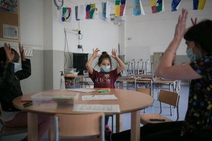 Una maestra con dos alumnas en una escuela de Barcelona, en junio.