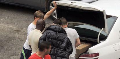 Un grupo de vecinos observa el interior de un maletero en el que, supuestamente, hay material robado.