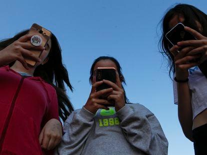 Un grupo de amigas con sus teléfonos móviles.